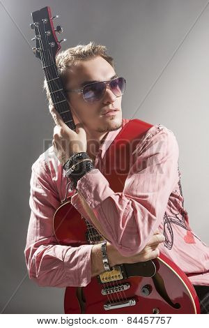 Portrait Of Thoughtful Caucasian Guitar Player With Stylish Guitar Standing Against Gray Background