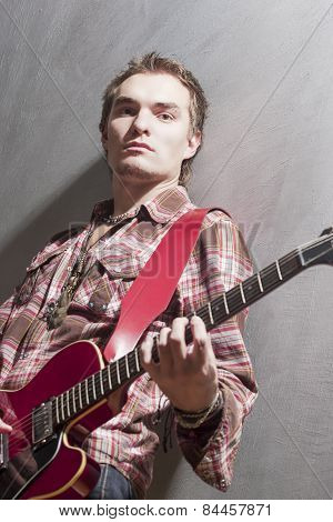 Portrait Of Thoughtful Caucasian Guitar Player With Stylish Guitar Standing Against Gray Wall