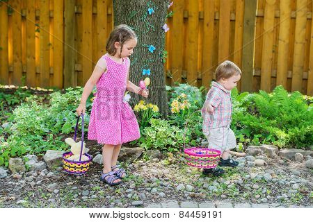 Girl And Little Boy Search For Easter Eggs