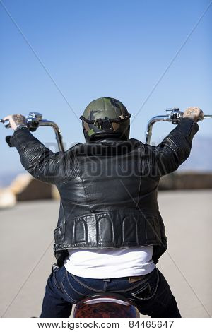 Rear View Of A Chopper Motorcyclist Riding .