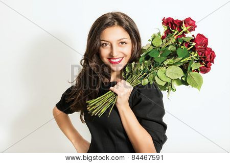Portrait of beautiful young cheerful woman with a bouquet of roses