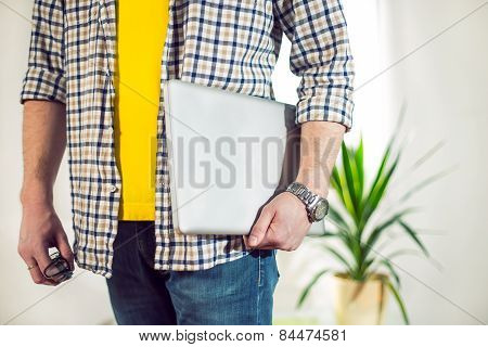 Hipster businessman with laptop standing Selective focus
