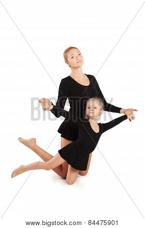Woman teaching kid dancing. mother and daughter are gymnastics