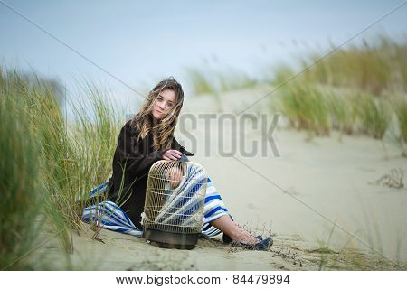 Beautiful Girl With A Birdcage In A Dune