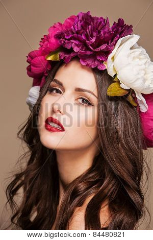 sexy model with curle hair and bright flowers on her head