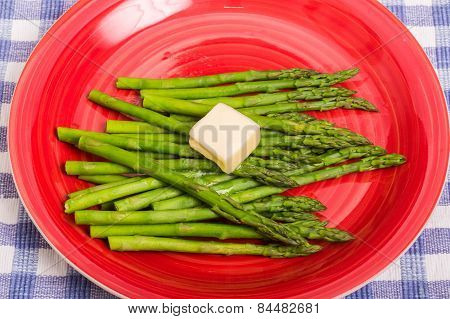 Green Asparagus On Red Plate With Butter