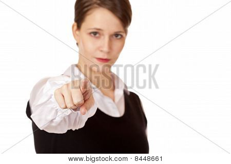 Serious looking businesswoman points with finger on camera.