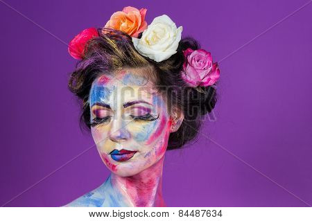 Beautiful cute girl decorated with colorful paints, hair roses.
