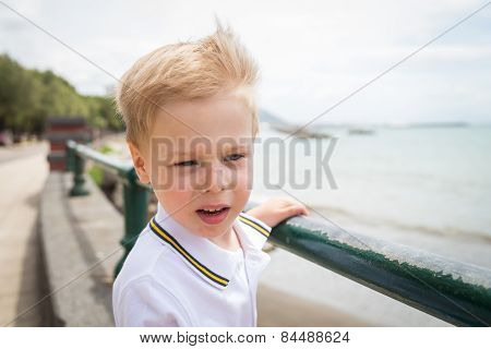 he boy looks at the sea from the coast.