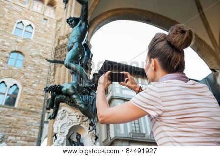 Young Woman Taking Photo Of Statue Perseus With The Head Of Medusa In Florence, Italy. Rear View