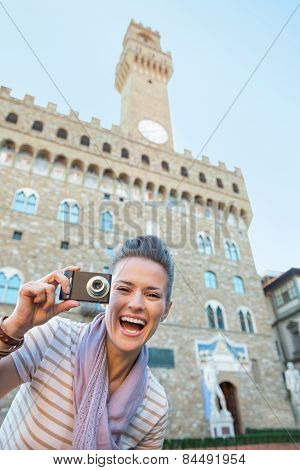Portrait Of Smiling Young Woman With Photo Camera In Front Of Pa