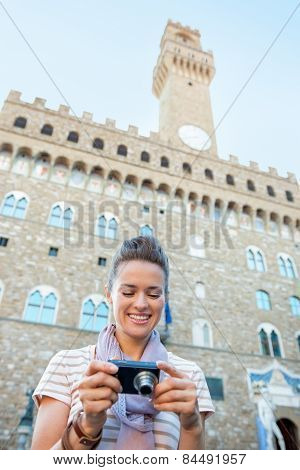 Happy Young Woman Checking Photos In Camera In Front Of Palazzo