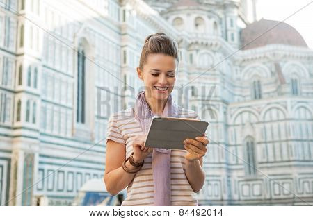 Happy Young Woman With Tablet Pc In Front Of Cattedrale Di Santa Maria Del Fiore In Florence, Italy