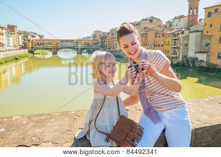 Happy Mother And Baby Girl Checking Photos In Camera On Bridge Overlooking Ponte Vecchio In Florence