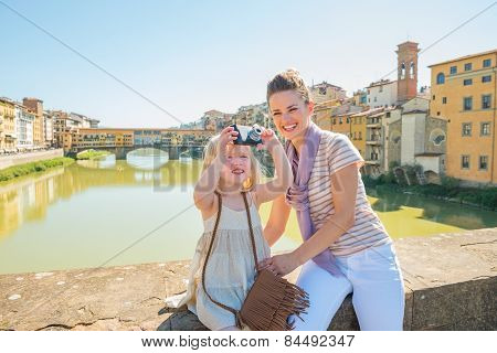 Mother And Baby Girl Taking Photo While Standing On Bridge Overl