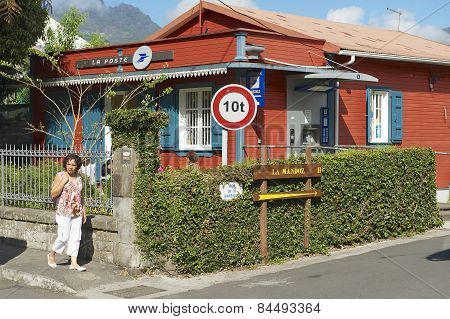 Woman walks by the street of Fond de Rond Point in Saint-Denis De La Reunion, France.