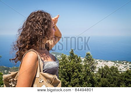Beautiful brunette looks into the distance at sea