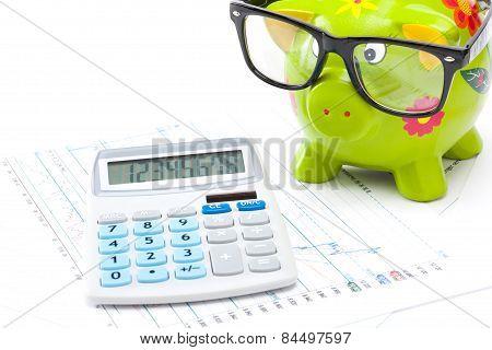Market Charts With Piggy Bank And Calculator Over It