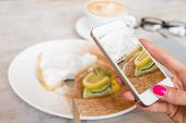 stock photo of cafe  - Woman taking photo of her cake in cafe with mobile phone - JPG