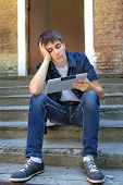 stock photo of boring  - Bored Teenager with Tablet Computer on the landing steps of the House - JPG