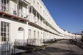 image of row houses  - A row of terraced houses part of the Royal York Crescent in Clifton Bristol UK which is reputed to be the longest Georgian crescent in Europe