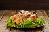 stock photo of bondage  - Bondage shibari roasted chicken with salad leaves on red plate on wooden background with dark space vertical - JPG