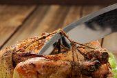 stock photo of bondage  - Bondage shibari roasted chicken on wooden background cutting cord closeup horizontal - JPG