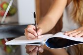 foto of writing  - Close up of a woman writer hand writing in a notebook at home in the kitchen - JPG