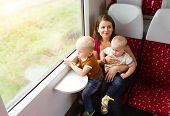 pic of lap  - Mother with sons in her lap traveling in train - JPG