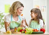 stock photo of child feeding  - kid daughter feeding mother vegetables in kitchen - JPG