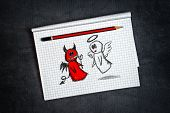 foto of maliciousness  - Angel And Devil Doodle Drawing on Notepad page as concept of conscience and moral dilemma in fight of good and evil - JPG