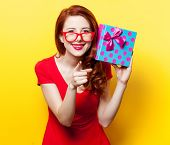 pic of redhead  - Redhead girl in red dress with glasses and gift box on yellow background - JPG