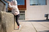 stock photo of hoodie  - Little girl with sneakers and hoodie training hard with a metal railing in a city square - JPG