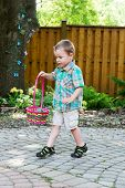 picture of easter basket eggs  - A cute boy holds a colorful Easter basket full of eggs he has found during an egg hunt in a garden in the spring - JPG