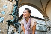 pic of perseus  - Smiling young woman in front of statue perseus with the head of medusa in florence italy - JPG
