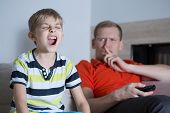 stock photo of annoying  - Little screaming son and his annoyed young father - JPG