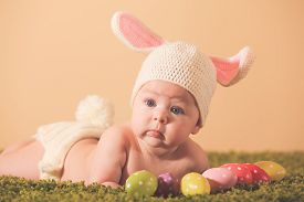 image of bunny costume  - Three months baby lying on his stomach as a Easter bunny on the grass with eggs - JPG