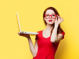pic of yellow  - Surprised redhead girl with laptop on yellow background - JPG