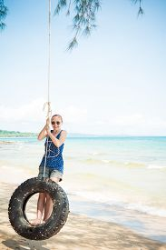 picture of tire swing  - Happy woman having fun on tire swing at the beach - JPG