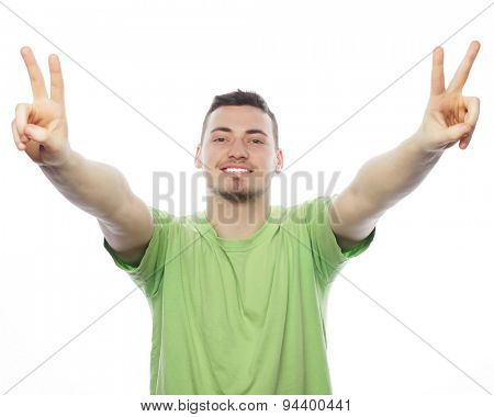 life style  and people concept: young casual man showing the victory gesture while smiling for the camera with a hand in his pocket.Isolated on white background