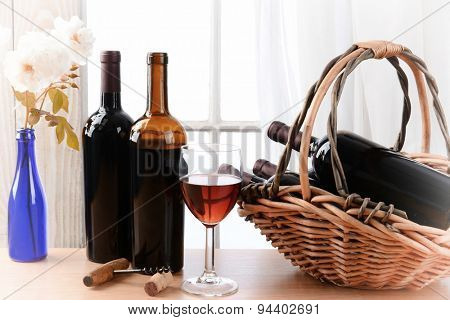 Wine still life with a basket of bottles and a glass of red wine and white roses in a vase on a table in front of a window with curtains. Horizontal format with vignette filter effect.
