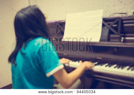 Blurred image ; Girl's hands on the keyboard of the piano : Vintage filter