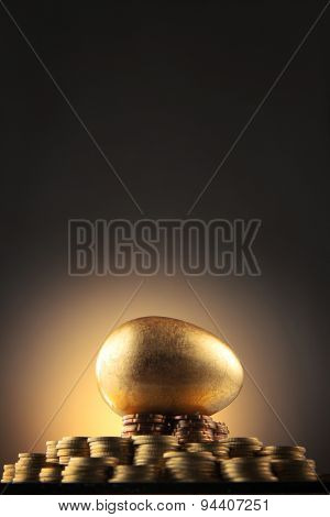 golden egg rest on stacks of coins