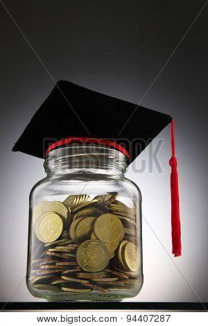 Bottle of cash with graduation cap.