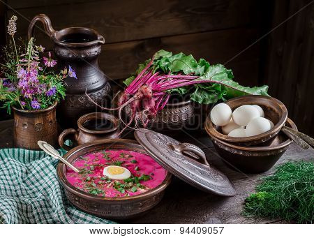 Russian Cold Soup With Beetroot, Bowl,spoons,jug,greenery On Dark Wooden Table.