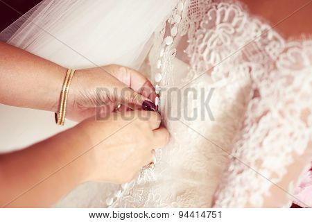 Hands Helping The Bride With Wedding Dress