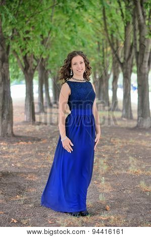 Young Brunette Girl In A Beautiful Blue Dress.