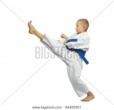 Boy in karategi beats kick leg forward