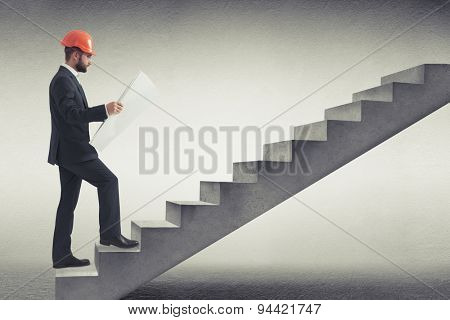 businessman in orange hardhat holding blueprint and following up on concrete stairs in grey empty room