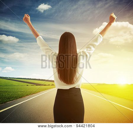 back view of happy woman raising hands up over road, green fields and sky